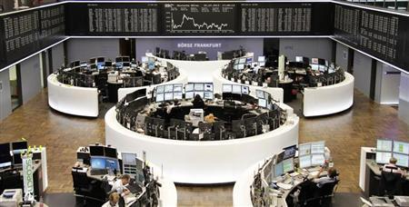 Traders work at their screens in front German share price index DAX board at the Frankfurt stock exchange