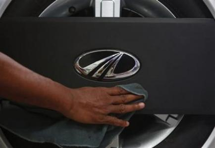 A showroom attendant cleans a Mahindra Quanto car inside the company's showroom in Mumbai
